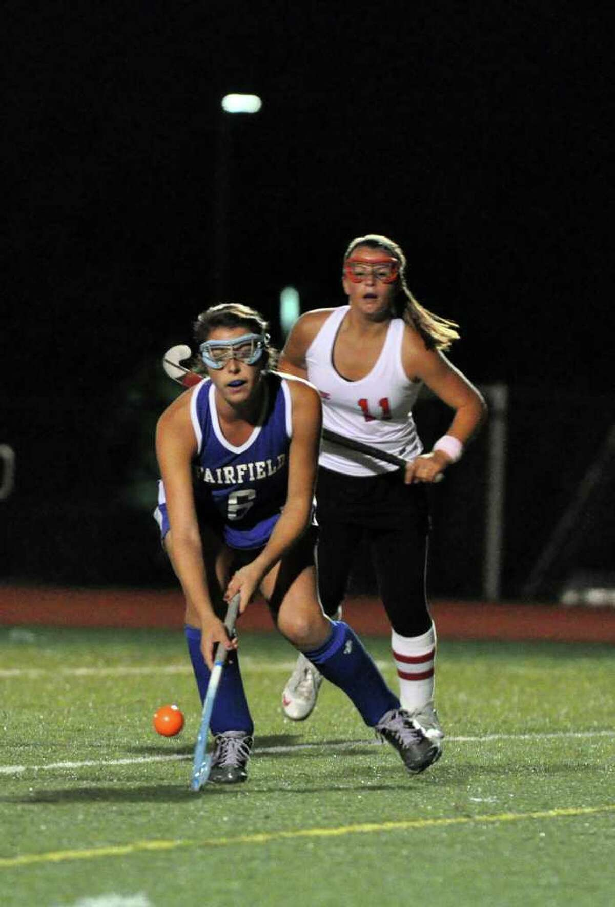 Fairfield Ludlowe's Meredith McGann takes control of the ball as Fairfield Warde's Stacey DiLeo chases after during the field hockey game at Warde on Thursday, Oct. 7, 2010.
