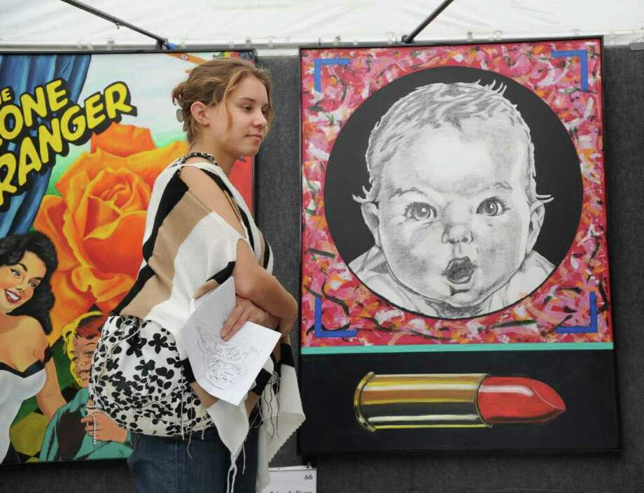 """Adrienne Harris of Harrison, N.Y. takes a look at the art of Brian Sullivan of Champaign, Illinois, during the Bruce Museum's 29th annual Outdoor Arts Festival, Greenwich, Saturday morning, Oct. 9, 2010.  The piece at right is an oil painting titled, """"Baby Gerber,"""" and is priced at $6,500. Photo: Bob Luckey / Greenwich Time"""