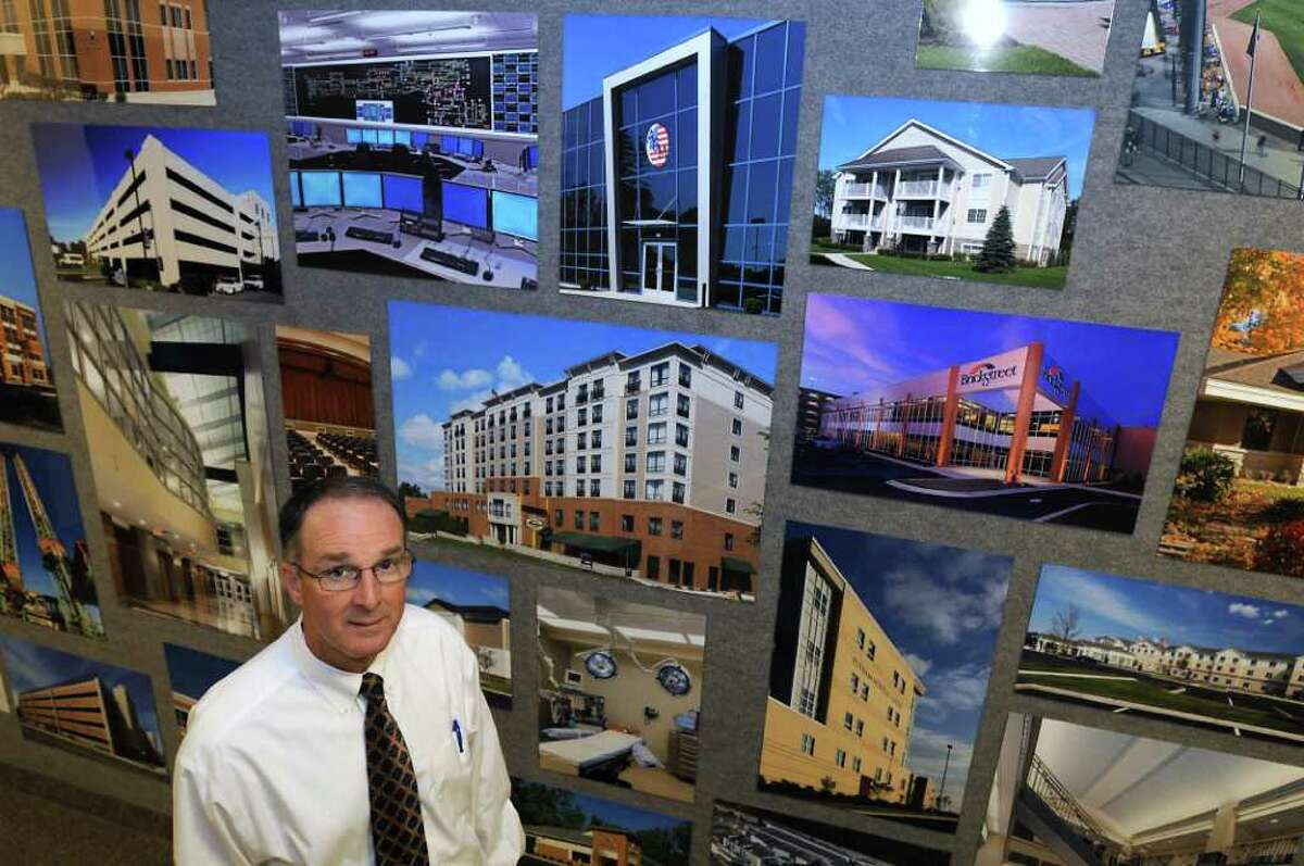 Kevin Gleason, President, stands by a wall of photos from past BBL projects at BBL Construction Services in Albany, NY on October 8, 2010. (Lori Van Buren / Times Union)