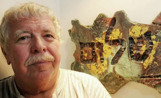 "Sculptor Paul Bouchard with his artwork at the House of Creative Soul gallery in Saratoga Springs, NY, on Tuesday, Oct. 5, 2010. It's part of ""The NYFA Mark 10 Artists of Troy"" show. The piece in the background is part of a series of three foam insulation sculptures, with gold leaf, paint, pumice, sand and wood, carved with symbols of peace from Hebrew and Arabic, inspired by his efforts to cope with Post Traumatic Stress Disorder after serving in the U.S. Navy during Vietnam. (Luanne M. Ferris / Times Union) Photo: Luanne M. Ferris"