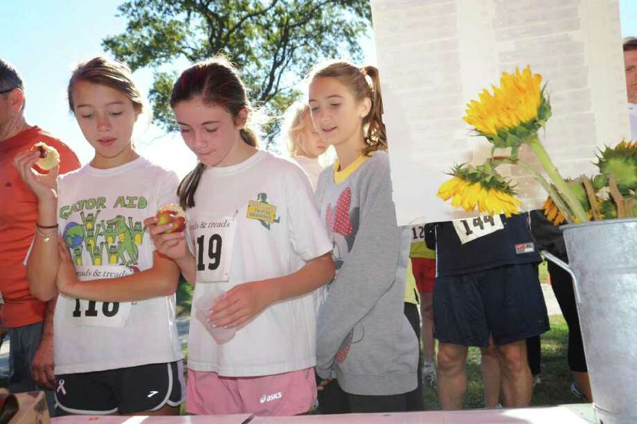 Olivia Bastianich, 12, left, Juliette Haroche, 13, and Lindsay Quackenbush, 13, all Greenwich Academy students check their time at Susannah Chase race on Greenwich Point, on Sunday, Oct. 10, 2010. Photo: Helen Neafsey / Greenwich Time