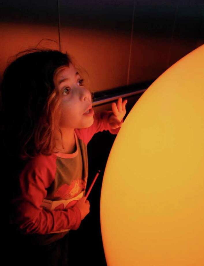 """Six-year-old Ariel Yarmus, of Cornwall on Hudson,  enjoys """"Elevator Music 17"""", and Peter Edwards' """"Spector, 2010,"""" while riding the elevator to view """"Ten Hours of Tang"""", at the Tang Museum on Sunday in Saratoga Springs.  Spector is made of plastic orbs, electronics, microcontrollers, hardware LEDs, aluminum & microphones, and was part of the full day of activities,exhibition, and presentations to celebrate the 10th Anniversary of the Tang Museum, on the campus of Skidmore College.   (Luanne M. Ferris / Times Union ) Photo: Luanne M. Ferris"""