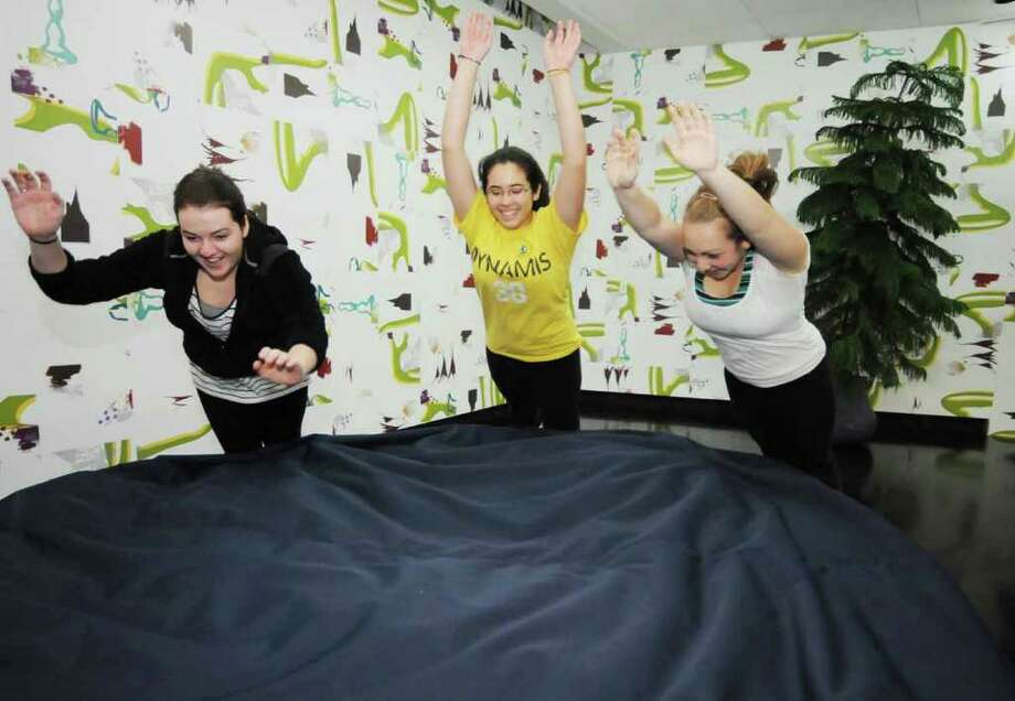 """Skidmore Freshmen, L-R: Amanda Nelson, of Madison, Wis., Alexandria Dorgan, of Boston, Mass, and Lindsey Decker, of Guilderland, jump into a huge bean bag that is part of the exhibit, """"Understory"""", by Paula Hayes, presented in one of the galleries for  """"Ten Hours of Tang"""", at the museum on Sunday in Saratoga Springs.  The exhibition was part of the full day of activities,exhibition, and presentations to celebrate the 10th Anniversary of the Tang Museum, on the campus of Skidmore College. (Luanne M. Ferris / Times Union ) Photo: Luanne M. Ferris"""