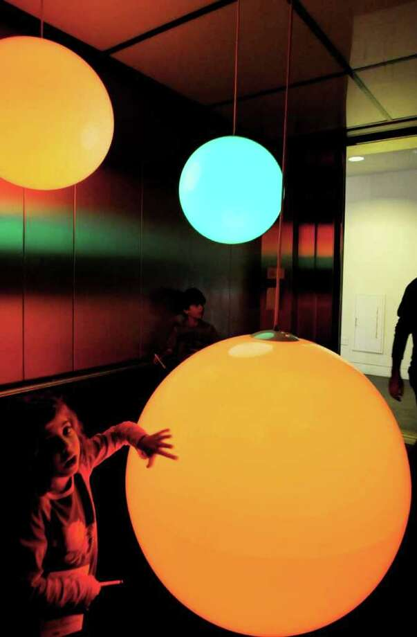 "Six-year-old Ariel Yarmus, of Cornwall on Hudson, enjoys ""Elevator Music 17"", and installation piece by Peter Edwards, called ""Spector, 2010,"" on her ride in the elevator to view ""Ten Hours of Tang"", at the museum on Sunday in Saratoga Springs.  Spector is made of Plastic orbs, electronics, microcontrollers, hardware LEDs, aluminum & microphones, and was part of the full day of activities,exhibition, and presentations to celebrate the 10th Anniversary of the Tang Museum, on the campus of Skidmore College.  (Luanne M. Ferris / Times Union ) Photo: Luanne M. Ferris"