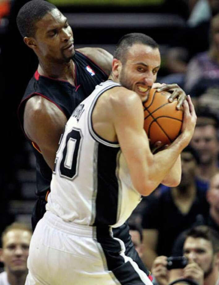 Spurs guard Manu Ginobili rips the ball away from Chris Bosh of the Miami Heat in the first half Saturday night.