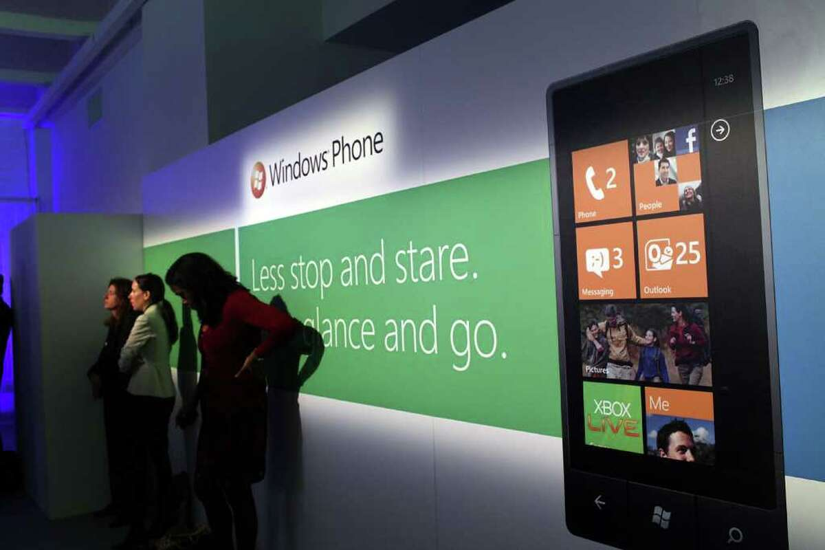 NEW YORK - OCTOBER 11: People attend the opening of the new Windows Phone 7 mobile operating system on October 11, 2010 in New York, New York. The phone, which will be available in the United States on AT&T's network, looks to compete with the iPhone, Android and BlackBerry smartphones. (Photo by Spencer Platt/Getty Images)