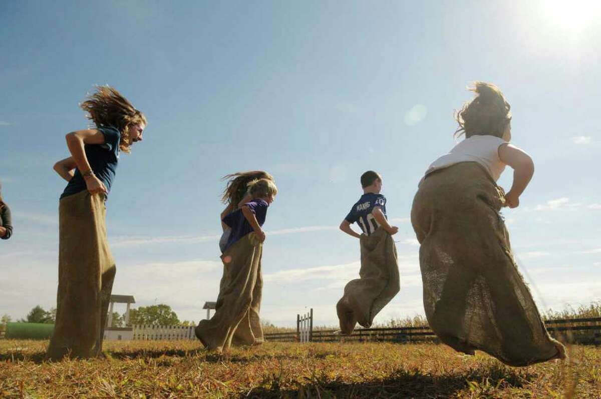 From left, Olivia Leonard, 11; Morgan Treacy, 13; Collin Treacy, 10; Adam Leonard, 9, and Acelynn Lewis, 7, take off in the potato sack race as part of the Family Farm Olympics at Liberty Ridge Farm in Schaghticoke, NY, on Monday, Oct. 11, 2010. (Paul Buckowski / Times Union)