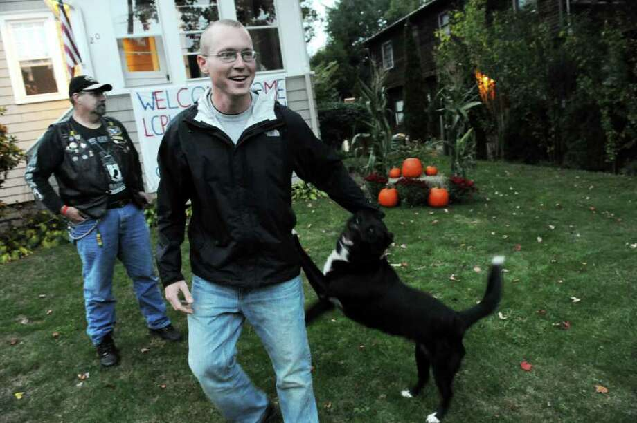 Lance Corporal William Markelon, 23, gets a welcome home from his family's dog Casey as Vietnam Veteran Warren Schlicker looks on Monday, October 11, 2010. Markelon arrived home from a 7-month tour in Afghanistan and was escorted from LaGuardia Airport to his Norwalk home by the Patriot Guard Riders. Markelon will return to  North Carolina's Camp LeJeune in three weeks. Photo: Keelin Daly / Stamford Advocate