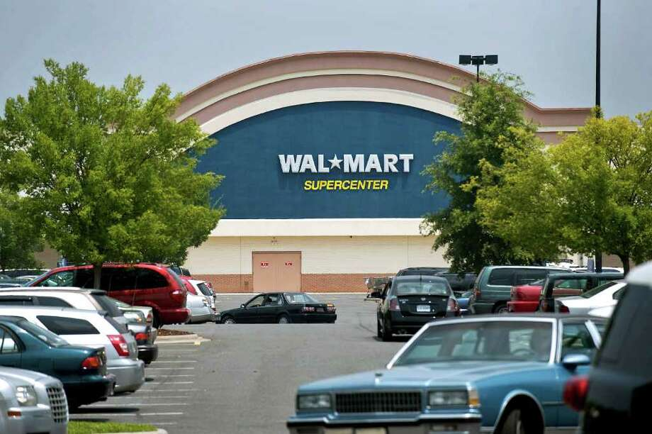 Customers drive through the parking lot of a Wal-Mart Supercenter store located about a mile from a new Family Dollar store that opened on May 6 in Charlotte, North Carolina, U.S., on Friday, July 9, 2010. Wal-Mart Stores Inc. is beginning to lose its grip on cash-strapped Americans. Dollar General Corp., Family Dollar Stores Inc. and Dollar Tree Inc. - competitors that are the biggest of the so-called dollar store chains - have all seen traffic at their stores tick up this year, while Wal-Mart's U.S. numbers have slipped. Photographer: Davis Turner/Bloomberg Photo: Davis Turner, Bloomberg / © 2010 Bloomberg Finance LP