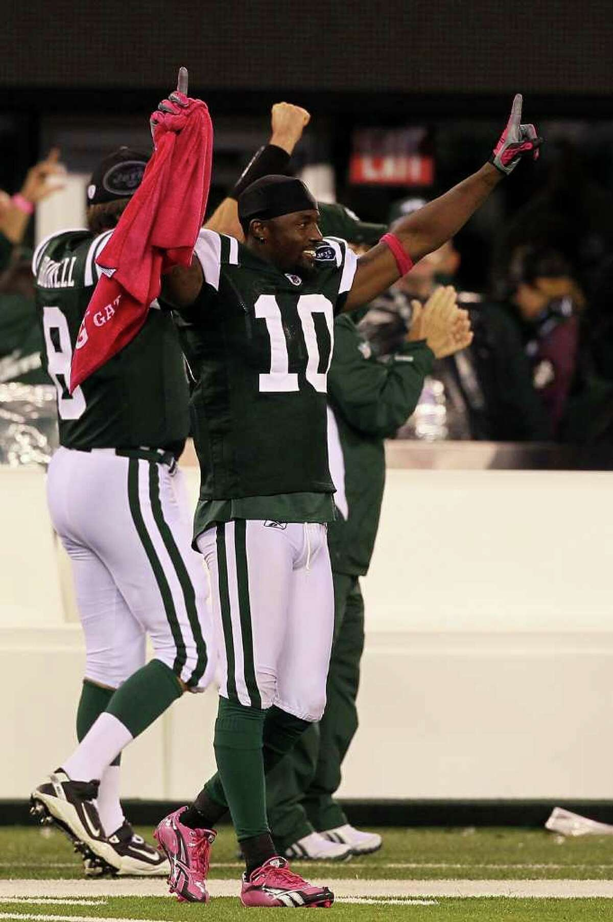 EAST RUTHERFORD, NJ - OCTOBER 11: Santonio Holmes #10 of the New York Jets celebrates as Dwight Lowery #26 scored on a 26-yard interception return for a touchdown in the fourth quarter against the Minnesota Vikings at New Meadowlands Stadium on October 11, 2010 in East Rutherford, New Jersey. (Photo by Jim McIsaac/Getty Images) *** Local Caption *** Santonio Holmes