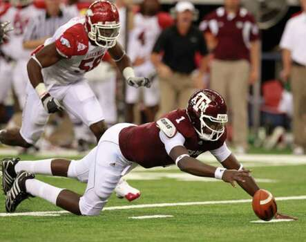 Texas A&M quarterback Jerrod Johnson reaches for his own fumble during the Aggies' loss to Arkansas on Saturday. Johnson failed to regain control and Arkansas recovered.