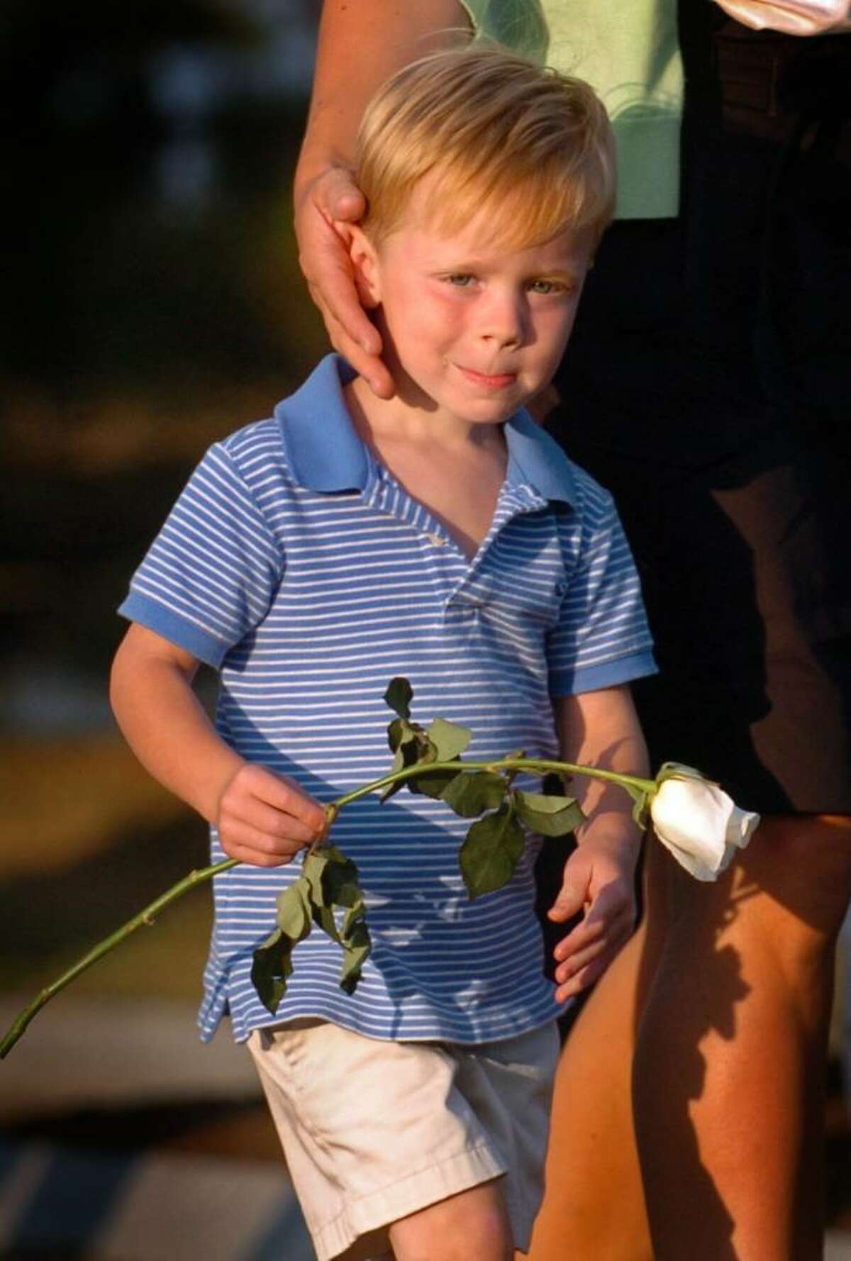Four-year-old Colin Woodward, of Fairfield, Conn., carries a rose to place on the monument of his uncle Bill Hunt during the annual September 11 memorial ceremony Wednesday Sept. 9, 2009 at Sherwood Island State Park in Westport, Conn.