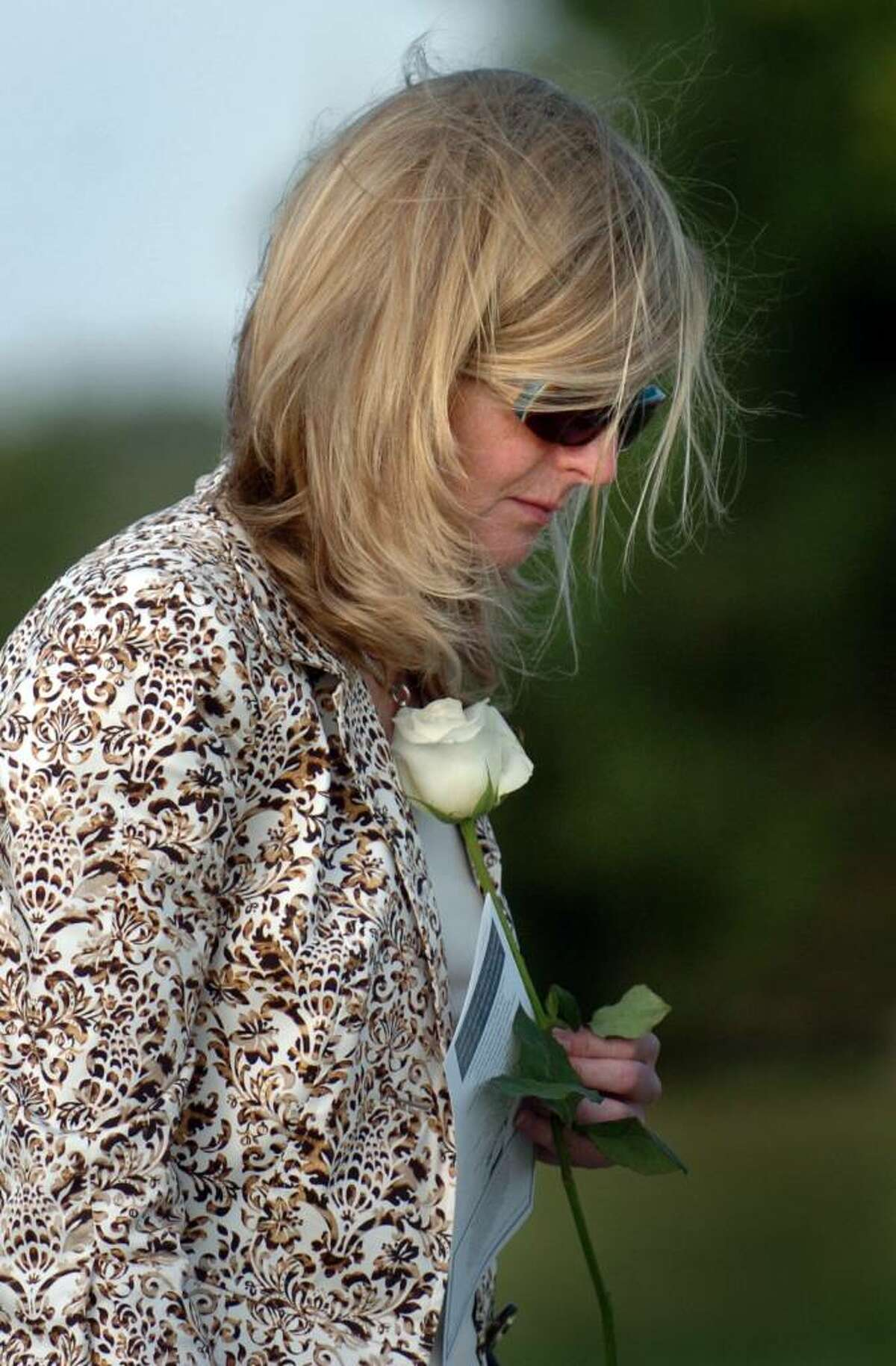 Susan Gardner, of Darien, takes a moment before placing a rose on her late husband Christopher Garner's name on the state's 9/11 Living Memorial during the annual ceremony Wednesday Sept. 9, 2009 at Sherwood Island State Park in Westport, Conn.