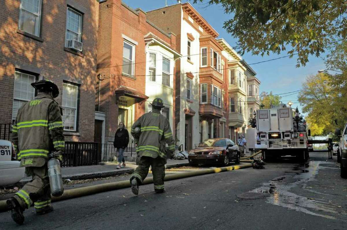 Firefighters make their way to the scene of an apartment fire Tuesday at 379 8th St. in Troy. (Paul Buckowski / Times Union)