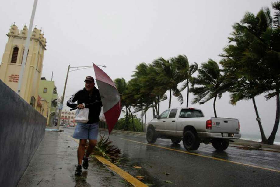 Luis Colon uses an umbrella to shield himself from rain and wind caused by the approaching Hurricane Earl in San Juan, Puerto Rico, Monday Aug. 30, 2010. (AP Photo/Andres Leighton) / AP