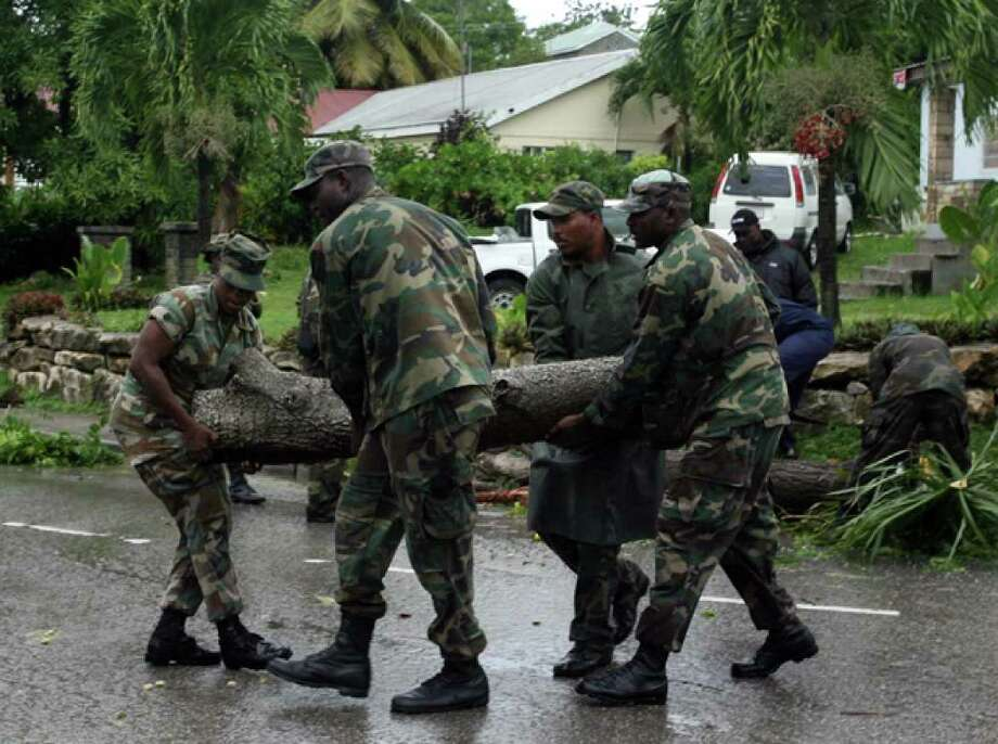Army soldiers help to remove a fallen tree at the village of Liberta after the passage of Hurricane Earl near Antigua, Monday, Aug. 30, 2010. Earl battered some islands across the northeastern Caribbean with heavy rain and roof-ripping winds Monday, rapidly intensifying into a major Category 3 storm on a path projected to menace the United States. (AP Photo/Johnny Jno-Baptiste) / AP