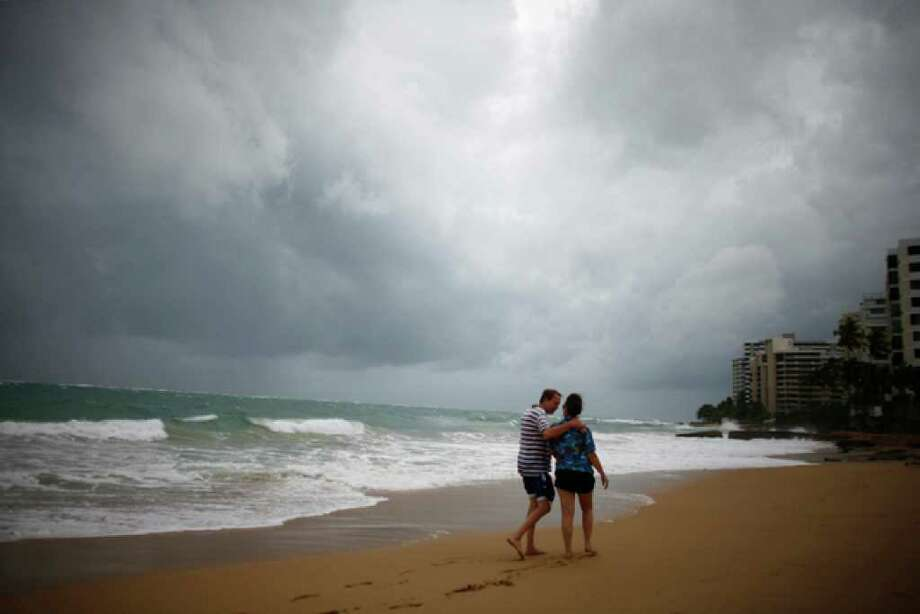 Tourists walk along the beach in the Condado neighborhood under cloudy skies caused by the approaching Hurricane Earl in San Juan, Puerto Rico, Monday Aug. 30, 2010. (AP Photo/Ricardo Arduengo) / AP