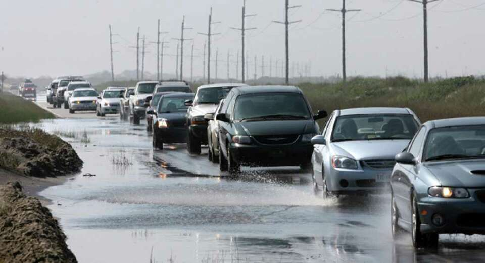 A line of cars heads north on Highway 12 through some ocean overwash near the north end of Hatteras