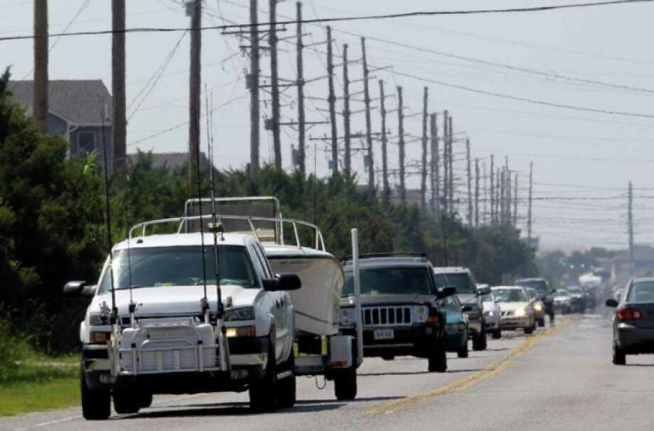 Cars drive north on Highway 12 in Avon, N.C., Wednesday, Sept. 1, 2010 as Hurricane Earl moves closer to the east coast. Tourist evacuations are underway on Hatteras Island and Ocracoke Island as Earl moves closer North Carolina's Outer Banks. (AP Photo/Gerry Broome) / AP