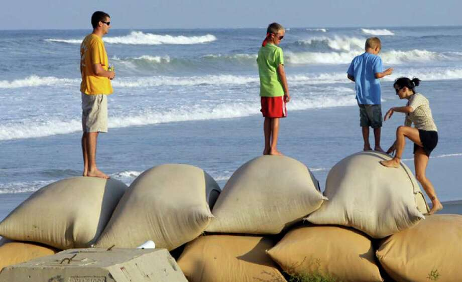 Chase Woolridge, from left, Whit Lombardo, Tyler Woolridge, and Jennifer Magner climb on sand bags along the southern beach in Nags Head, N.C., Wednesday, Sept. 1, 2010. Hurricane Earl continues to make it's way towards North Carolina's Outer Banks. (AP Photo/Gerry Broome) / AP
