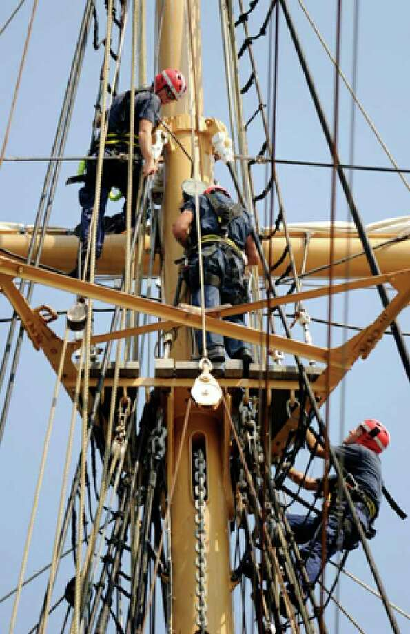 "Crewmen aboard the Coast Guard Barque Eagle work to ""house"" the top gallant mast as part of preparing the ship for hurricane Earl Wednesday, Sept. 1, 2010 in New London, Conn. The crew has spent the last two days bringing the ship to secure for sea status as well as ""housing"" the top gallant masts to allow passage under the Gold Star Bridge should they need to move Eagle to a pier at the Navy Sub Base. (AP Photo/The Day, Sean D. Elliot) / 2010 The Day Publishing Company"