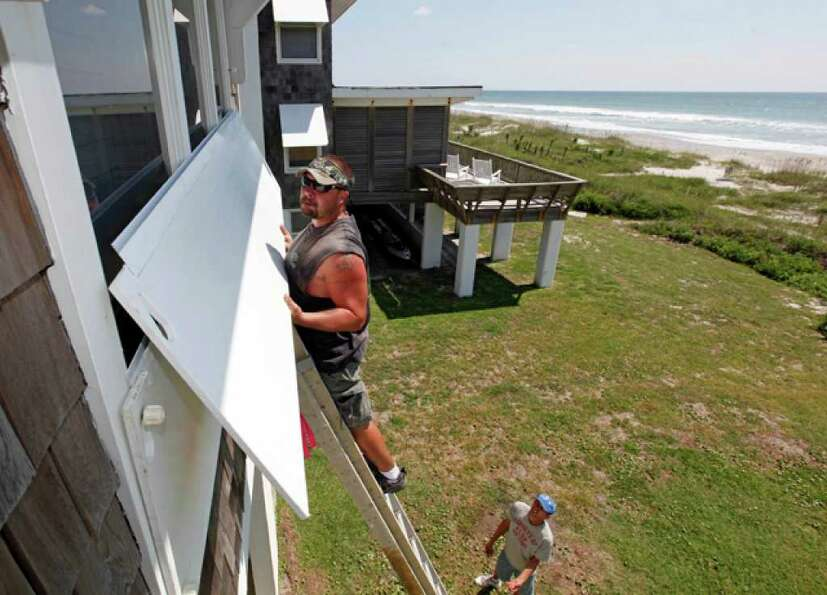 Jay Farley, top, installs covers to a homeowner's oceanfront window as Jason Wheeler, bottom, looks