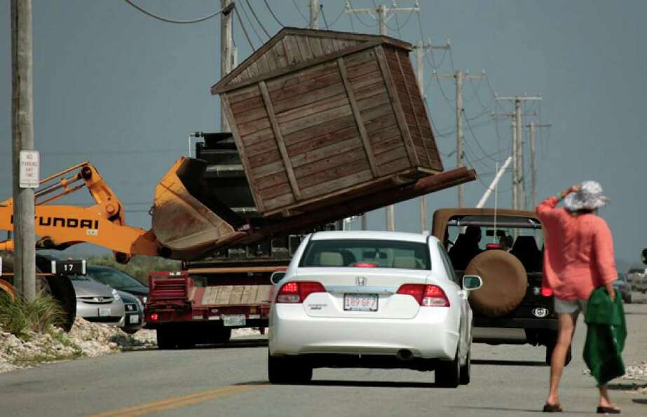 A portable building is removed from along East Beach Road in Westport, Mass., Thursday, Sept. 2, 201