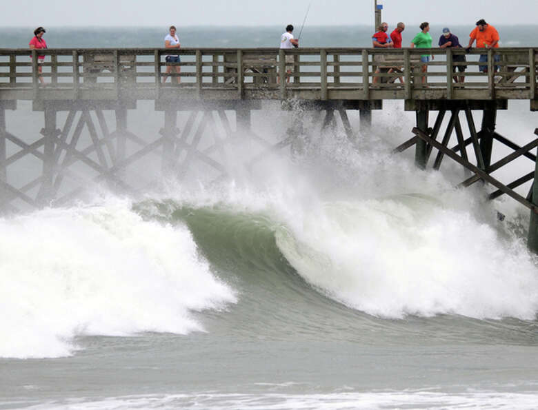 People stand on the Surf City Ocean Pier and watch the swells from Hurricane Earl in Surf City, N.C.