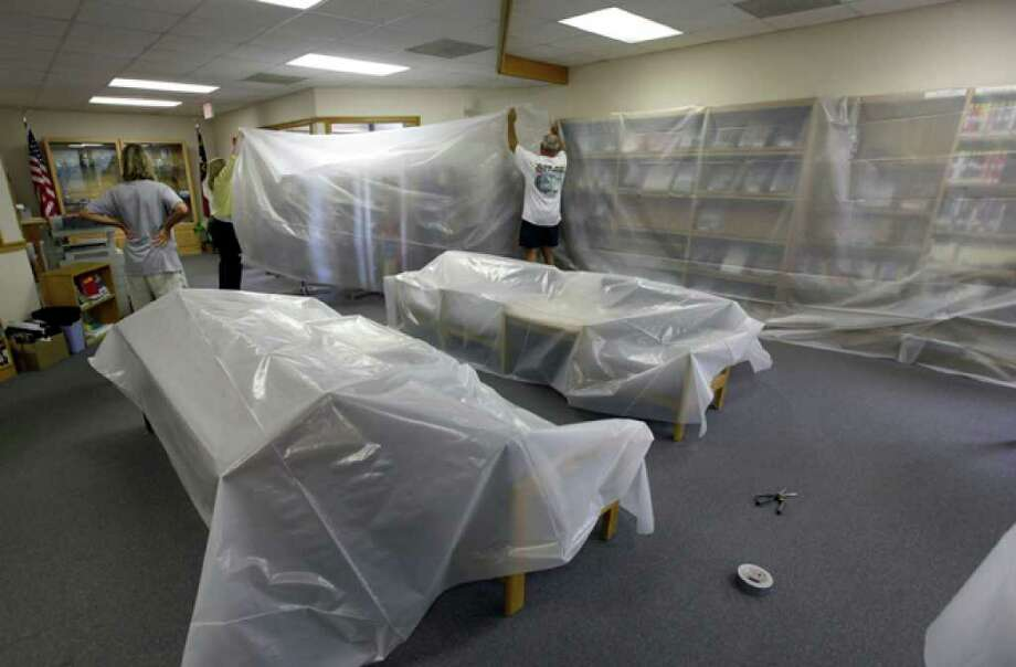Peter Flynn, right, Brita Flynn, left, and Melissa Bennett, center, cover books and desks with plastic sheeting at the Carteret Public Library as Hurricane Earl heads toward the eastern coast in Pine Knoll Shores, N.C., Thursday, Sept. 2, 2010. (AP Photo/Chuck Burton) / AP