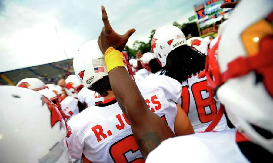 A Lamar football player holds up the Lamar hand sign as they gather in mid-field to get geared up be