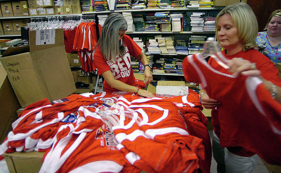 At the Kampus Corner Bookstore, employees Anissa Downer, left, and Amy Gorrell, right, rush to get new shirts onto hangers and out onto the sales floor.  The fever that is Lamar University's first home football game in over 20 years was especially evident in stores carrying anything Lamar related as people searched and bought their favorite Lamar merchandise.   Dave Ryan/The Enterprise