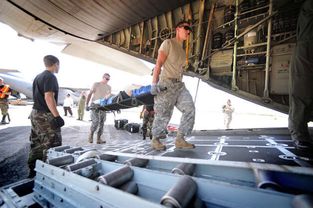National Guard units from Texas and Delaware load special needs patients onto a C-130 transport plane at the Southeast Texas Regional Airport.  The paitents were transported to San Antonio. Guiseppe Barranco