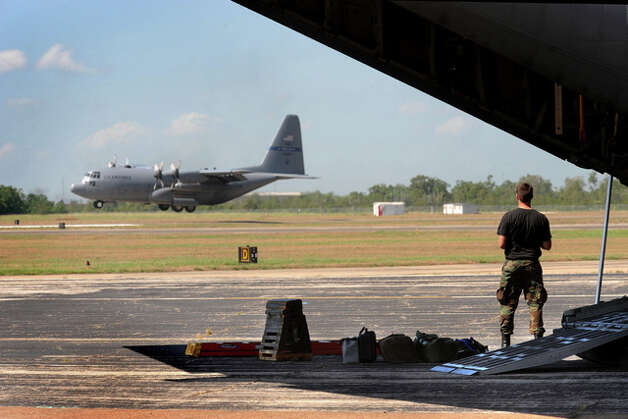 Joseph Oliphant with the Delaware National Guard watches as a C-130 transport plane touches down at the Southeast Texas Regional Airport.  More than 40 Texas National Guard members assisted in the airlfit. Guardsmen worked 24-hour shifts during hurricane preparation and recovery efforts. Guiseppe Barranco