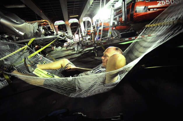 After working 18 hours, U.S. Coast Guard officer Chris Farrell relaxes in a hammock on the ship Cape Vincent at the Port of Beaumont. Guiseppe Barranco