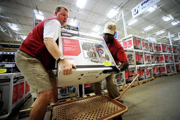 From left, Richard Odom and Travis Reed load a generator onto a cart at the Lowe's Home Improvement Warehouse. Guiseppe Barranco