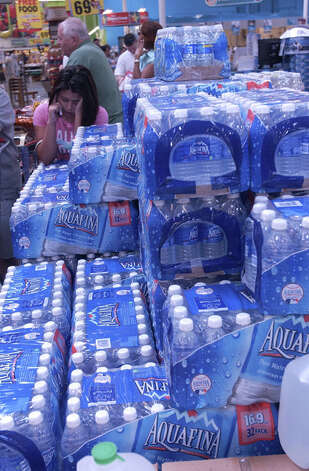 Jennifer Hinojosa leans on cases of bottled water in an aisle at a local grocery store as she talks on her cell phone while family members wait in long checkout lines before the storm. Dave Ryan