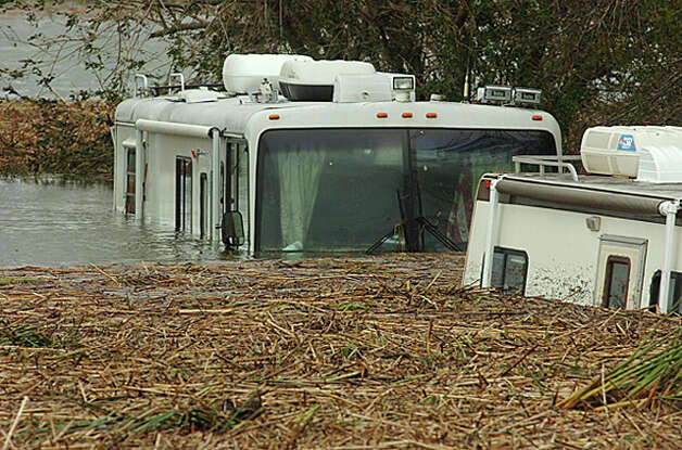 Floating marsh grass surrounds flooded motor homes off Texas 73 near Port Acres. Guiseppe Barranco