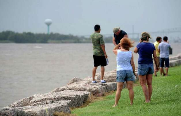 Winds whip around residents standing along Port Arthur's seawall watching the churning ship channel prior to the hurricane's landfall. Tammy McKinley