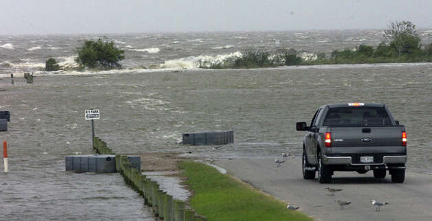 Sightseers watch the rising waves just past the RV park on Pleasure Island. Except for seagulls, the area was abandoned as the hurricane approached. Dave Ryan