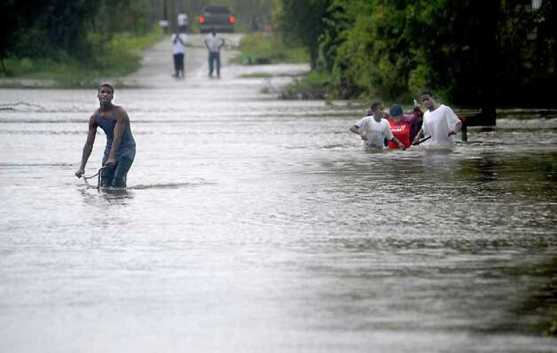 Local residents travel through flood waters near Pine Street. Tammy McKinley