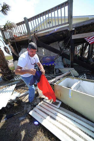 Allan Maniha retrieves a Texas flag from the debris surrounding his beach home.  Guiseppe Barranco