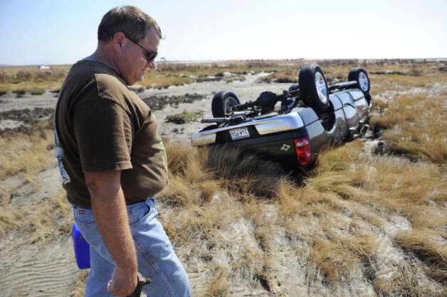 Near Gilchrist, Matt White pays solemn respect to an overturned Dodge truck that provided refuge for him and several others as they floated for almost an hour before being pulled from the storm surge by a U.S. Coast Guard helicopter rescue team.  Valentino Mauricio