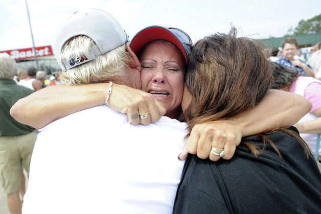 Crystal Beach resident, Laura Wolfford, center, has an emotional reunion with Paul Norton, left, and his wife, Cathy, right.  The three were reunited at an impromptu meeting for Bolivar Peninsula residents in a grocery store parking lot on Texas 124. Valentino Mauricio
