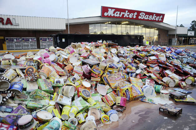 Dumped frozen food, only a fraction of the total that spoiled in homes and businesses left without electric power, fills the front parking lot of a grocery store on Texas 124. Valentino Mauricio