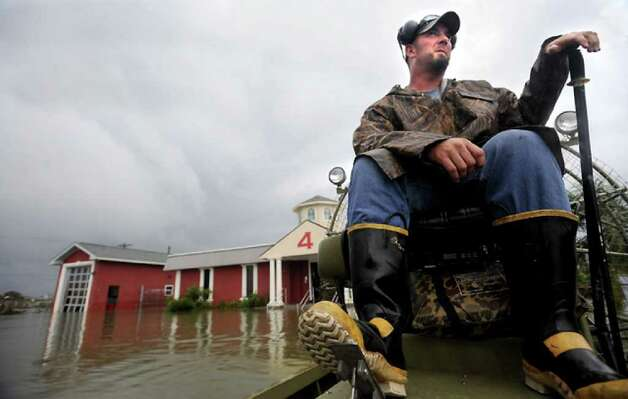 Volunteer rescue worker Bobby England surveys damage on an airboat. Tammy McKinley