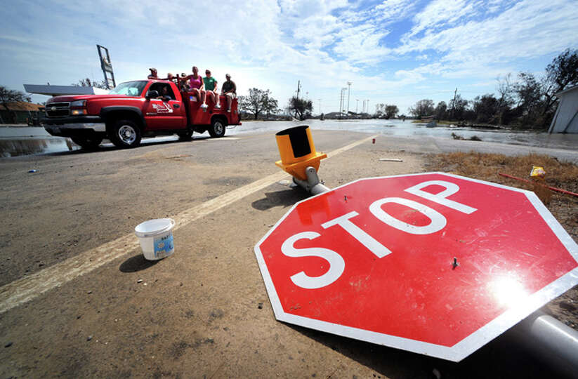 Traffic signs litter roadways as Sabine Pass residents travel in a group to survey property damage.