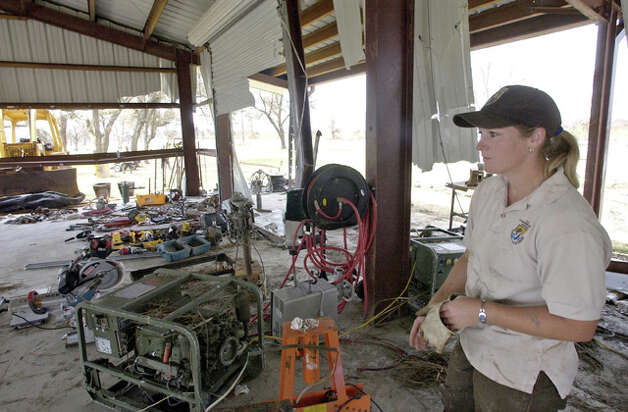 Jena Moon, of the U.S. Fish and Wildlife Service, gloves up to help a co-worker salvage what's left of a water-damaged workshed.  Dave Ryan