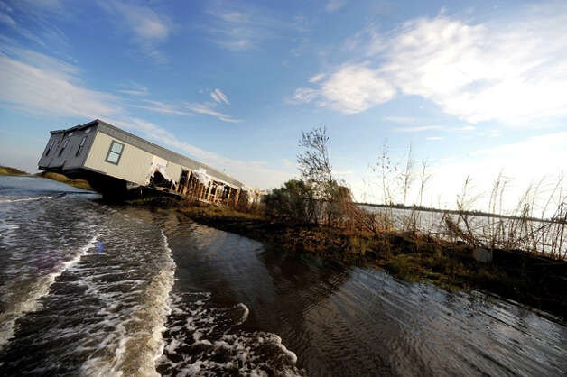 A mobile home hangs off of Texas 87 into the Sabine-Neches Waterway on the Monday after Ike made landfall. Guiseppe Barranco