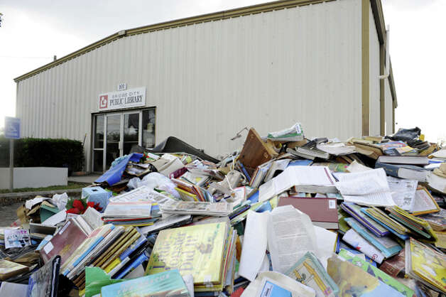 Soggy books form a colorful trash heap outside the water-damaged Bridge City Public Library. Valentino Mauricio