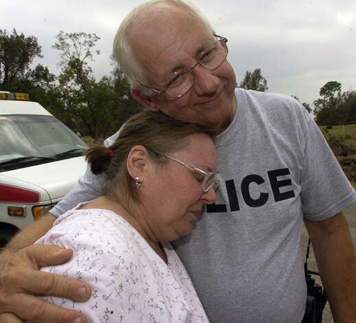 Dianne Brookshire gets a comforting hug from Bridge City Police Officer Ronnie Denton after seeing the destruction at her heavily damaged home. Dave Ryan